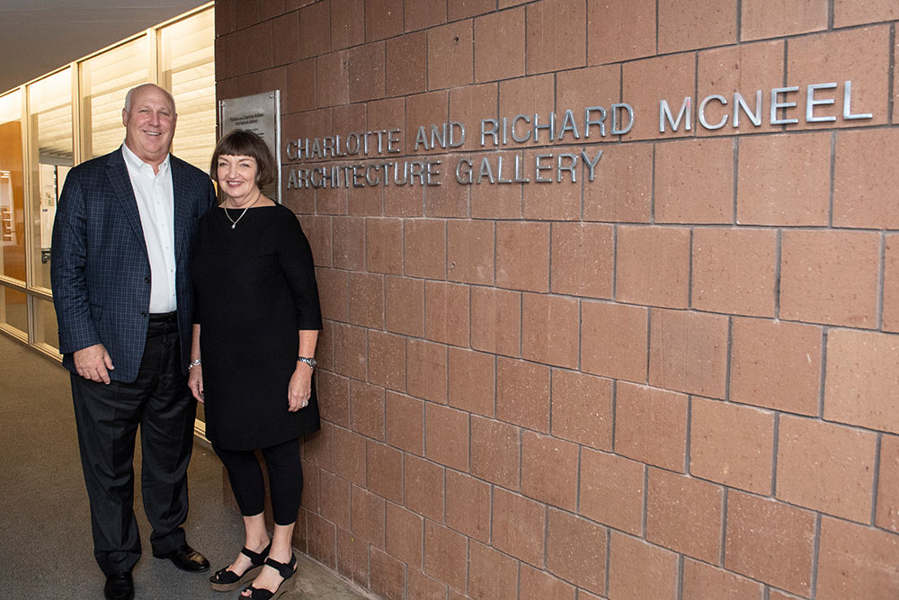 "left to right: Richard and Charlotte McNeel stand in front of the new letters for the gallery  ""Charlotte and Richard McNeel Architecture Gallery"""