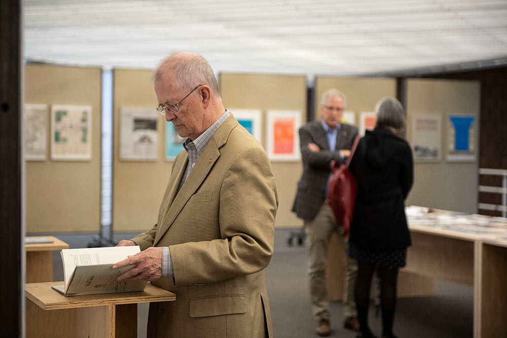man views book in the 40th anniversary exhibit in the Charlotte and Richard McNeel Gallery