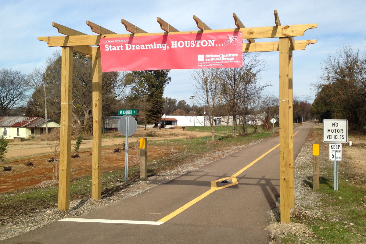 An arbor marks the southern terminus of the Tanglefoot Trail. The attached sign recognizes the CIRD project.