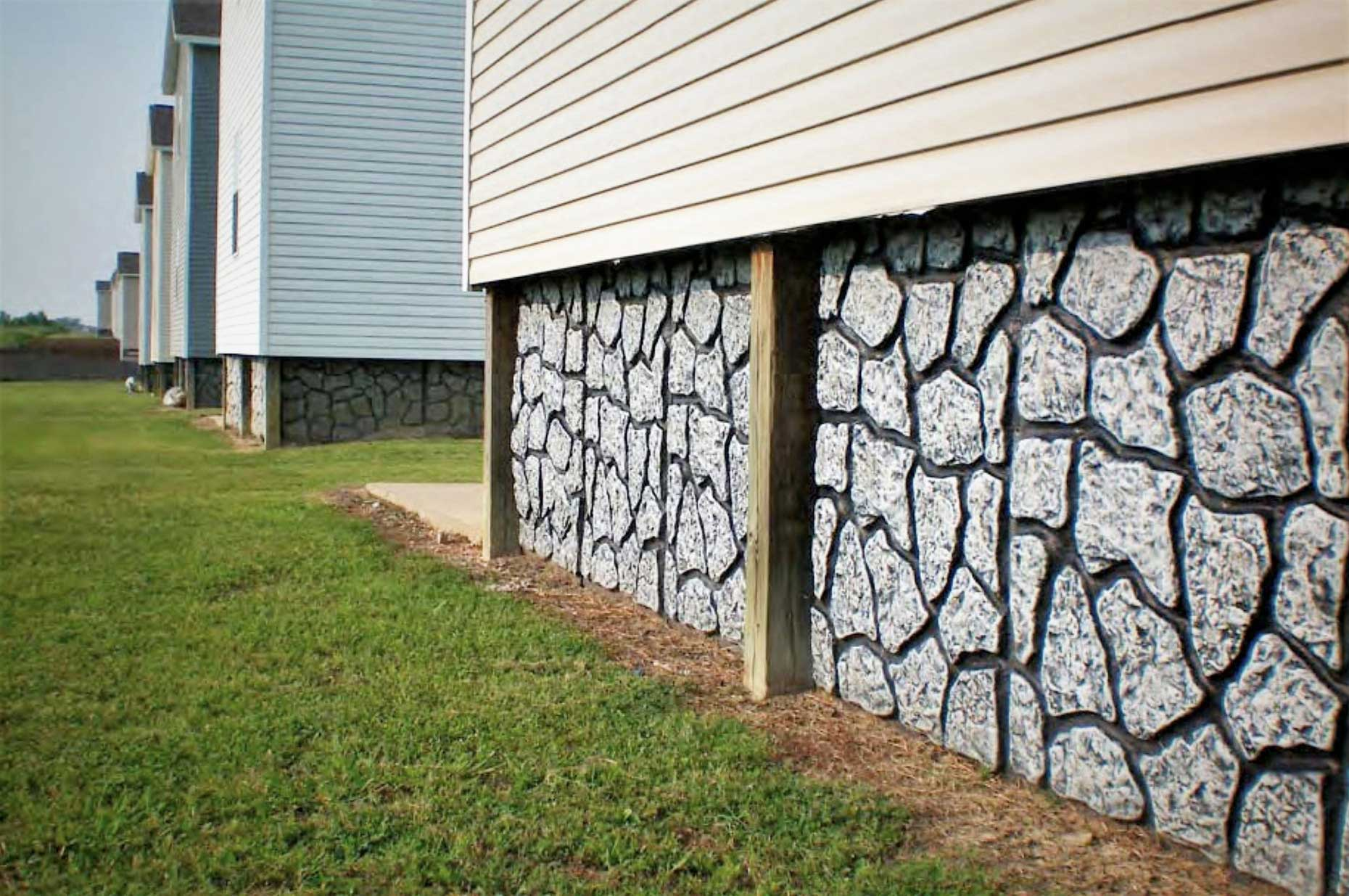 close up of rock wall acting as skirt around home